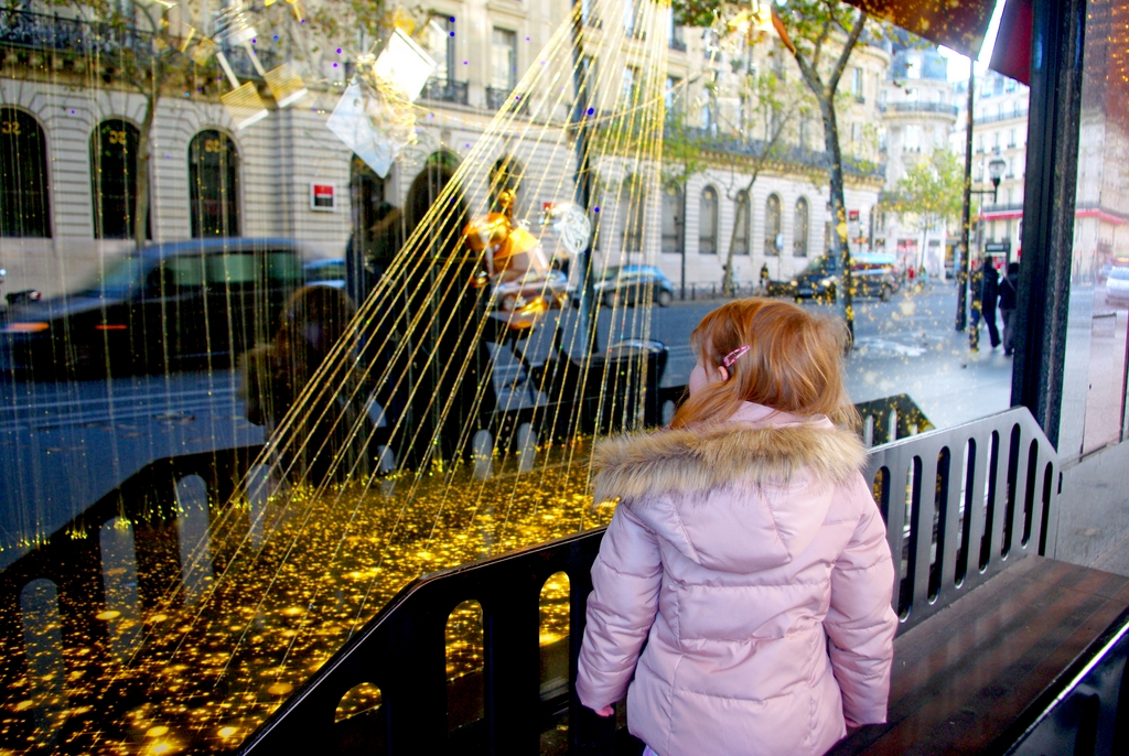 Little Girl in front of Christmas window display of Galeries Lafayette copyright French Moments